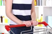 Woman with trolley in supermarket close-up — Stock Photo