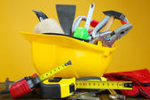 Construction equipment on wooden table, on color background — Stock Photo