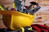 Construction equipment on wooden table on wall background — Stock Photo