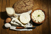 Still life with dairy products and bread on wooden table — Stock Photo