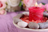 Composition with spa stones, candle  and flowers on color wooden table background — Stock Photo