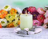 Composition with spa stones, candle  and flowers on color wooden table, on light background — Stock Photo