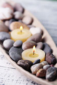 Spa stones and candle in decorative bowl, on color wooden background — Stock Photo