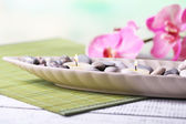 Spa stones and candle in decorative bowl, on wicker mat, on color wooden background — Stock Photo