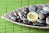Spa stones and candle in decorative bowl, on wicker mat background — Stock Photo