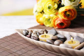 Spa stones and candle in decorative bowl, on bamboo mat, on color wooden table, on bright background — Stock Photo