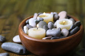 Composition with spa stones, candles on wooden background — Stock Photo