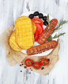 Grilled sausages on wooden table — Stock Photo