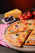 Tasty pizza on table on dark red background — Stock Photo