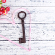 Key to love and happiness. Composition with key, ribbon and flowers. Conceptual photo. On color wooden background — Stock Photo