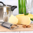 Composition with tasty spaghetti, grater, cheese, wine bottle and glass on wooden table, on light background — Stock Photo #43598279