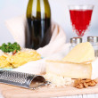 Composition with tasty spaghetti, cheese, wine bottle and glass on wooden table, on light background — Stock Photo