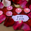 Beautiful red rose petals with candles and greeting card, close up — Stock Photo #43598523