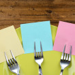 Empty note papers attached to forks, on plate, on color wooden background — Stock Photo