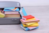 Books in suitcase on wall background — Stock Photo