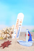 Thermometer  in sand on bright background — Stock Photo