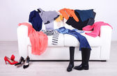 Messy colorful clothing on white sofa on white wall background — Stock Photo