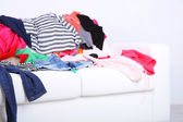 Messy colorful clothing on white sofa on white wall background — ストック写真