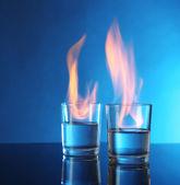 青色の背景にアルコールを燃焼とメガネ — ストック写真