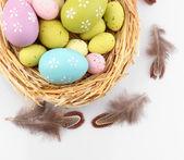 Ovos de Páscoa no ninho e penas decorativas, isoladas no branco — Fotografia Stock