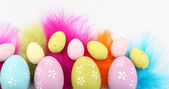Easter eggs and decorative feathers, isolated on white — Stock Photo