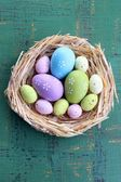 Easter eggs in nest on color wooden background — Stockfoto