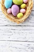 Easter eggs in nest on color wooden background — Stock Photo