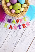 Easter eggs in nest and sign on color wooden background — Stok fotoğraf