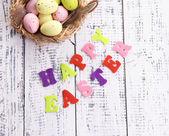 Velikonoční vejce v hnízdo a podepsat na barevné dřevěné pozadí — Stock fotografie