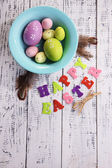 Easter eggs in color bowl , feathers and sign on color wooden background — Stock Photo