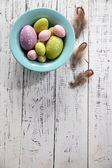 Easter eggs in color bowl on color wooden background — Stockfoto