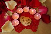 Vackra röda rosenblad med ljus och gratulationskort, närbild — Stockfoto
