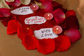 Beautiful red rose petals with candles and greeting card, close up — Stock Photo