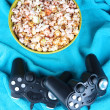 Black game controllers and bowl with pop corn on color plaid background — Stock Photo #43604299