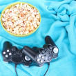 Black game controllers and bowl with pop corn on color plaid background — Stock Photo #43604301