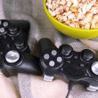 Black game controllers and bowl with pop corn on color plaid background — Stock Photo #43604311