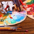 Artistic equipment: paint, brushes and art palette on wooden table — Stock Photo #43604899