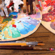 Artistic equipment: paint, brushes and art palette on wooden table — Stock Photo #43604927