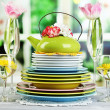 Stack of colorful ceramic dishes and flowers, on wooden table, on light background — Stock Photo #43606199