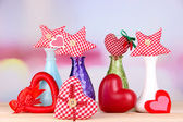 Hand-made textile hearts in different vases on wooden table, on light background — Stock Photo