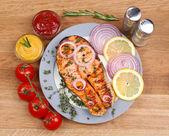 Tasty grilled salmon with vegetables, on wooden table — Stock Photo