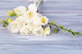 Beautiful freesias on wooden table — Stock Photo