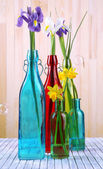 Beautiful irises and daffodils in bottles, on wooden background — Stock Photo