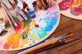Artistic equipment: paint, brushes and art palette on wooden table — Stock Photo