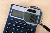 Fraud concept with magnifier and calculator, on wooden background — Stock Photo