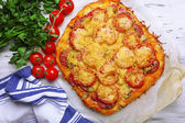 Homemade pizza on baking paper close up — Stock Photo