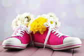Beautiful gumshoes with flowers inside on wooden table, on light background — Stock Photo