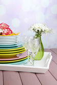 Stack of colorful ceramic dishes and flowers, on tray, on wooden table, on light background — Stock Photo