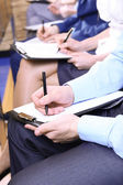 Hands holding pens and making notes at conference — Stock Photo