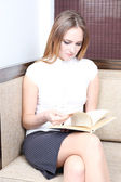 Young businesswoman sitting on couch in office and reading book — Stock Photo